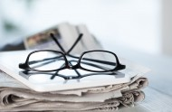 50019243 - stack of newspapers, eyeglasses and digital tablet